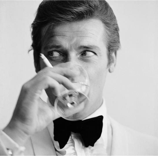 roger-moore-well-known-for-his-roles-as-james-bond-and-the-saint-downs-a-martini-1968-photo-by-peter-ruckbipsgetty-images